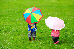 Kids with colorful umbrellas on rainy day Royalty Free Stock Photos