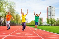 Kids in colorful uniforms with arms up running. The marathon on the finish line on the stadium Royalty Free Stock Images