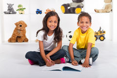 Kids coloring in. Two happy indian kids coloring in with crayons on books in bedroom Royalty Free Stock Photo