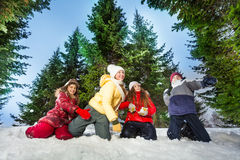 Kids competes in throwing snowballs at winter wood Royalty Free Stock Photography