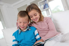 Kids complicity. Children reading book at home stock photography