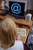 Kids and computer. A girl win front of a computer monitor with symbol of e-mail over it stock photography