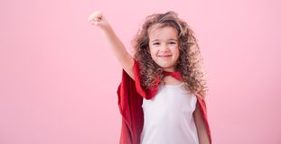 Kids concept, smiling girl playing super hero. The concept of children, a smiling curly-haired girl playing a super hero, pointing up , isolated on pink stock images
