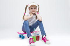 Kids Concepts. Portrait of Little Caucasian Blond Girl in Visor. Sitting on Pink Pennyboard With Two Cups of Juice. Against White. Horizontal Image Stock Photos
