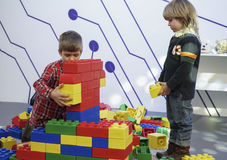 Kids constructing a man from the building blocks. Two boys constructing a men from the building blocks Royalty Free Stock Photos
