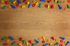 Kids construction toys screws and nuts on wooden background. Top view. Flat lay. Copy space for text Royalty Free Stock Photography