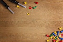 Kids construction toys tools: colorful screwdrivers, screws and nuts on wooden background. Top view. Copy space for text Stock Image