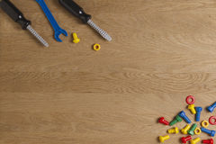 Kids construction toys tools: colorful screwdrivers, screws and nuts on wooden background. Top view. Flat lay. Copy Stock Photos