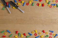 Kids construction toys tools: colorful screwdrivers, screws and nuts on wooden background. Top view. Flat lay. Copy Stock Photography