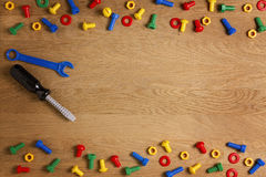 Kids construction toys tools: colorful screwdrivers, screws and nuts on wooden background. Top view. Flat lay. Copy Stock Image