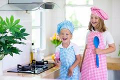 Kids cook in white kitchen. Children cooking stock photo