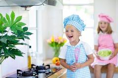 Kids cook in white kitchen. Children cooking stock photos