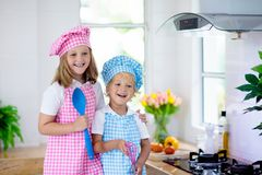 Kids cook in white kitchen. Children cooking royalty free stock photography