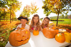 Kids in costumes during Halloween craft pumpkins Royalty Free Stock Images