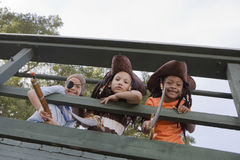 Kids In Costumes Looking Through Wooden Railings Stock Photography