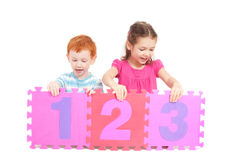 Kids counting 123 with number tiles stock images