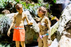 Kids covered in mud. Kids brother and sister covered in mud in front of beautiful waterfall traditional tourist activity on St Lucia island in Caribbean royalty free stock image