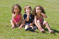 Kids Covering Mouths. Three young children sitting on grassy lawn covering their mouths as if blowing kisses, being quiet, or eating food Stock Photos