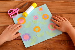 Kids crafts - applique with paper flowers. Child put his hands on a desk. Child made crafts. Scissors, glue. Paper crafts. Kids summer crafts stock photo