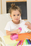 Kids crafts. Beautiful little girl cutting paper with scissors on the art lesson class. Children education concept Royalty Free Stock Photo