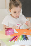 Kids crafts. Beautiful little girl cutting paper with scissors on the art lesson class. Children education concept. Learn Study Education School Knowledge Royalty Free Stock Photography