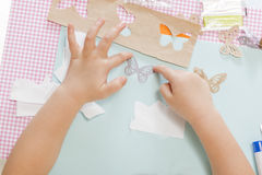 Kids crafts. Little child hands sticking butterfly paper on the art lesson class. Children education concept. Learn Study Education School Knowledge Concept royalty free stock photos