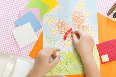 Kids crafts. Little child hands sticking pieces of paper mosaic on the art lesson class. Children education concept. Learn Study Education School Knowledge Royalty Free Stock Photography
