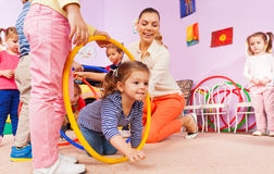 Kids crawl though hoop with teacher and friends Stock Photo