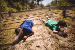 Kids crawling under the net during obstacle course. In boot camp stock photography