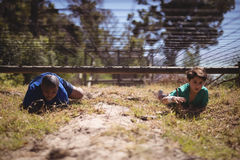 Kids crawling under the net during obstacle course. In boot camp royalty free stock photography