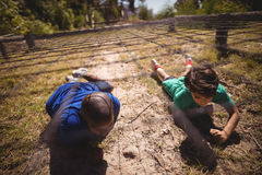 Kids crawling under the net during obstacle course. In boot camp royalty free stock images