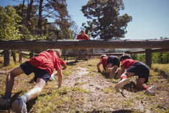 Kids crawling under the net during obstacle course training. In the boot camp stock images