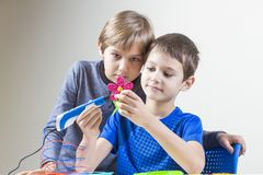 Two boys creating with 3d printing pen. Kids creating with 3d printing pen new object royalty free stock photos