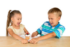 Kids and a cupcake. A girl and a boy are fighting over a single delicious cupcake stock image