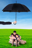 Kids and dad reading book under umbrella. Image of two children and their father reading a book under umbrella on the meadow. Life insurance concept Royalty Free Stock Image