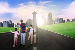 Kids and dad walking on the road with upward arrow Royalty Free Stock Photo