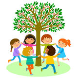 Kids dance around a tree Stock Photo