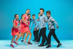 The kids dance school, ballet, hiphop, street, funky and modern dancers. On blue studio background Royalty Free Stock Photo