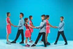 The kids dance school, ballet, hiphop, street, funky and modern dancers. On blue studio background Stock Images