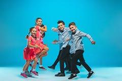 The kids dance school, ballet, hiphop, street, funky and modern dancers. On blue studio background Stock Image