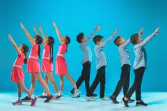 The kids dance school, ballet, hiphop, street, funky and modern dancers. On blue studio background Royalty Free Stock Photography