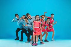 The kids dance school, ballet, hiphop, street, funky and modern dancers. On blue studio background Royalty Free Stock Images