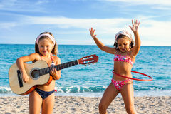 Kids dancing and singing with guitar on beach. Close up portrait of two little girls in swimwear dancing and singing with guitar on beach Stock Photography