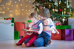 Kids in a dark room with a beautiful Christmas tree Royalty Free Stock Photography