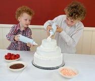 Kids Decorating Cake stock photo