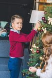 Kids decorating christmas tree. Brother and sister decorating christmas tree together Royalty Free Stock Photography