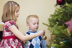 Kids decorating a Christmas Tree. Two kids enjoying the Holidays by decorating a Christmas Tree together Royalty Free Stock Photo