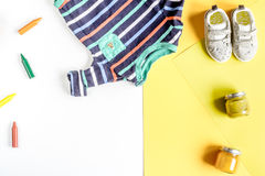Kids desk design with toys and clothes yellow white background top view mockup Stock Photos