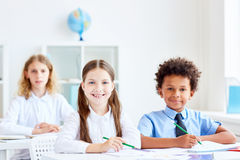 Kids by desks. Three intercultural youngsters with pencils sitting by desks Royalty Free Stock Photo