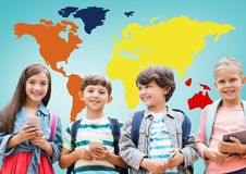 Kids on devices in front of colorful world map. Digital composite of Kids on devices in front of colorful world map Royalty Free Stock Image